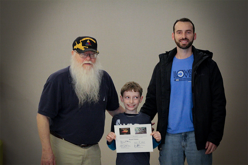Jim Hollingsworth (left) promoting Noah Mahan (center) to Sergeant in the Texas Chess Militia.  Noah's proud Father, Joel Mahan, is on the right.