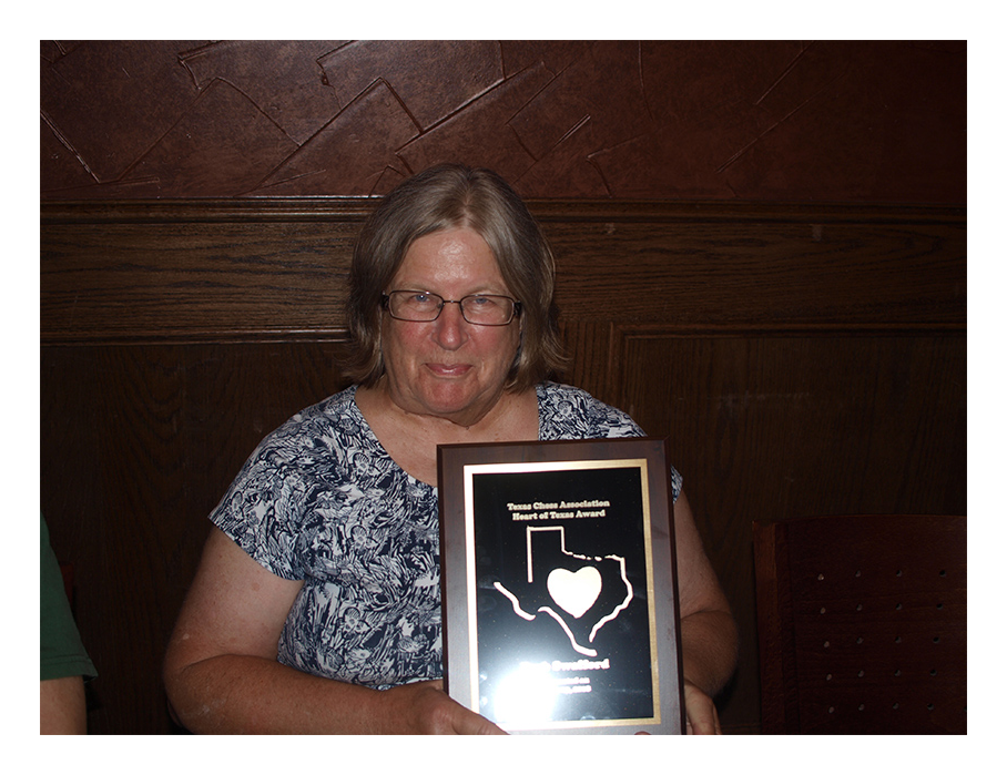 Barb Swafford, Texas Chess Association Treasurer and Secretary/Treasurer of the Dallas Chess Club, Holding her Heart of Texas Award