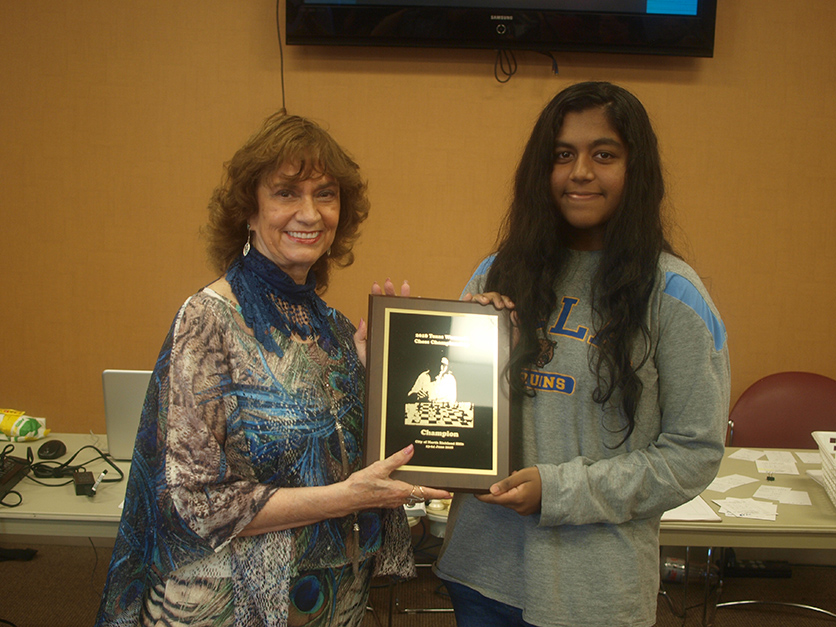 Maritta Del Rio Sumner presenting the Texas Women's Chess Champion award and title to WFM Devina Devagharan