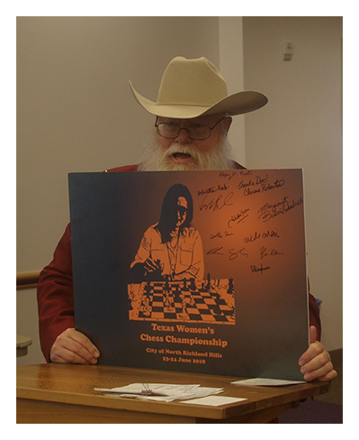 Jim Hollingsworth with poster autographed by all The 2018 Texas Women's Chess Championship players